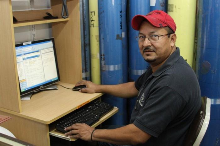 Con su computador, donde diseña las muestras de las cajas.
